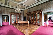 The library at Corvey – a harpsichord and antique cabinets with intarsia in a cordoned-off section with herringbone parquet flooring, for visitors a deep pink carpet
