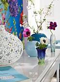 Anemonen und Blütenzweig in Vasen vor einem Dekopaneel mit floralem Design