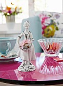 A painted porcelain figurine of flower girl on a round, reflective magenta table