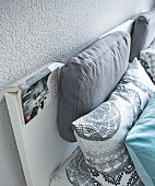 Fat pillows on a simple headboard of a double bed against a grey wall