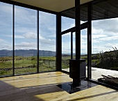 Modern, empty living room with free standing wood burning stove and panoramic view