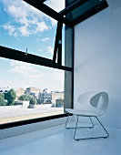 White shell stool in designer style on a white floor in front of a bank of windows with a view