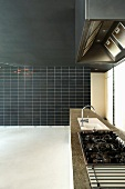 Extra long kitchen unit and floor to ceiling, black, partially tiled wall