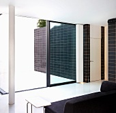 Black sofa in front of an open patio door and view of a black tiled wall in front of a white floor