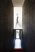 Narrow staircase with black tiled walls and a view down the stairs of a entry way
