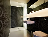 Dramatic bath with black tiled walls and recessed strip lighting in the wall over the wash basin