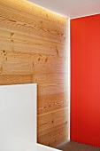 Corner of a room with one wall painted a shade of red and a wood paneled wall