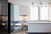 Open plan designer kitchen with white counter across from a stainless steel countertop