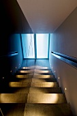 Narrow stairway with illuminated stairs and a view of the entrance door