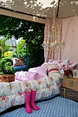 A comfortably furnished tent with colourful cushions and picnic baskets