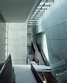 Flights of stairs illuminated through ceiling in tall, modern building with exposed concrete walls and reflective wall cladding