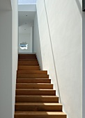 Simple staircase in hard, tropical wood with white walls and small, decorative cut out in wall