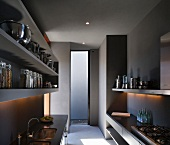 Grey, minimalist kitchen with integrated sink, gas hob and plain shelving with stainless steel and glass vessels