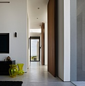 Corridor in South American house with yellow glass vases on polished concrete floor and floor-to-ceiling panels of exotic wood