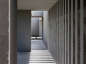 Collage of grey stripes and light formed by wall elements and apertures outside a South American house