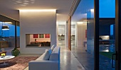 Twilight in living area of glass-walled, South American residence with view of adjacent dining area through wall element