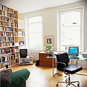 A wall of books across from a home office with a desk chair covered in black leather in front of a window in the living room