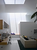 Desk and wall-mounted, wooden cupboard on a wall in a modern living room with a couch under a skylight