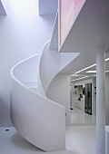 Curved staircase with white brick banister next to an open hallway with a view of the kitchen