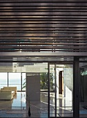 Modern facade of a new building with metal louvres and glassed in first floor with a view of a minimalist living room