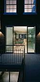 Wohnhaus in Abendstimmung mit offenen Terrassentüren und Blick in beleuchtetes Esszimmer