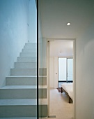 White lacquered stairs with glass dividing wall and view through an open bedroom door