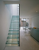 View of the glass stairs of a stairway and glass dividing wall in an open designer kitchen with dining area