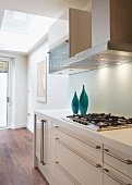 Blue vases on a white, modern, kitchen countertop with stainless steel pulls and exhaust hood