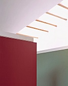Corner of wall panel painted in a shade of red in front of a gray wall under a skylight in contemporary architecture