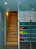 Lobby with colorful plastic shoes in metal shelves next to a wooden staircase