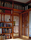 Library in Asian style with open door and wood lattice with a view of a staircase