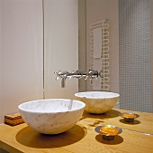 Marble wash basin on a wooden countertop and designer fittings from the mirrored wall