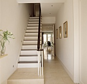 Narrow, white lacquered wooden staircase and dark railing in a stairwell with open door and view into a dining room