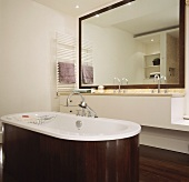 Free standing bathtub clad in dark wood in front of a minimalist vanity and mirror