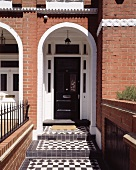 Entry way with a round arch in the brick facade of an English row house