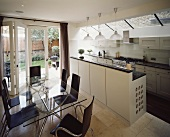 Modern, open kitchen with white countert and shell chairs made of dark wood around a glass top dining table and a wall of patio doors