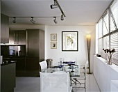 Set dining table and white sailcloth chairs in front of an open stainless steel kitchen