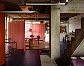 Industrial hall with concrete construction and circular room divider around an dining table with a pink curtain