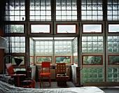 Industriehalle mit Glasbausteinwand und verschiedenen Stühlen im Schlafbereich
