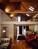 Living room in a converted attic with mezzanine and wood paneling on the ceiling