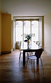 Glass top dining table and retro shell chairs in front of a window in Art Nouveau style