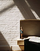 Doll in a former fireplace and whitewashed brick wall