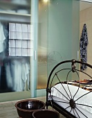 Antique metal bed stead and ceramic pots at the end of the bed in front of the sliding glass doors of the bathroom ensuite