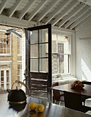 Open balcony door in vintage style in a designer kitchen with white, wooden ceiling