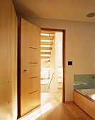 Designer bath with bathtub next to an open wooden door in Japanese style