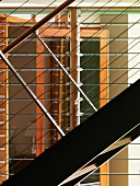 Detail of a metal stairway with railings and horizontal wire cables