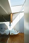 White, rattan, designer lounger in the corner of a room