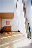 Minimalist living room with a light curtain in front of a tall window