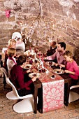 A party eating Christmas dinner in a vaulted cellar