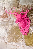 A pink stag decoration on a stone wall